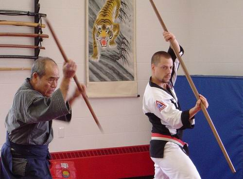 Grandmaster trains Renshi Brown in traditional bo techniques